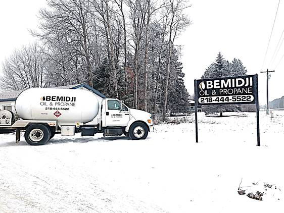 Bemidji Oil and Propane Truck next to sign in the winter